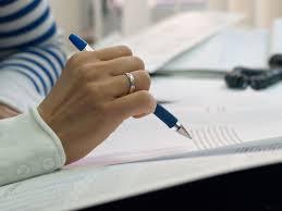Relecture et main de femme tenant un stylo